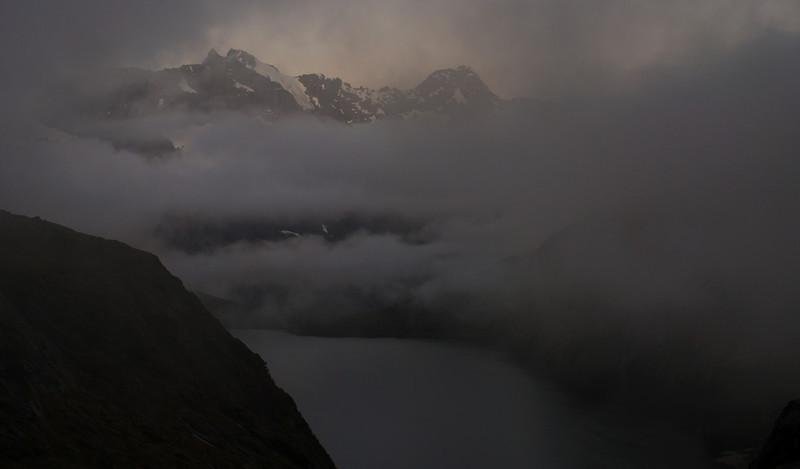 Taiaroa Peak and Mount Tuhawaiki poke through the cloud in the last evening light
