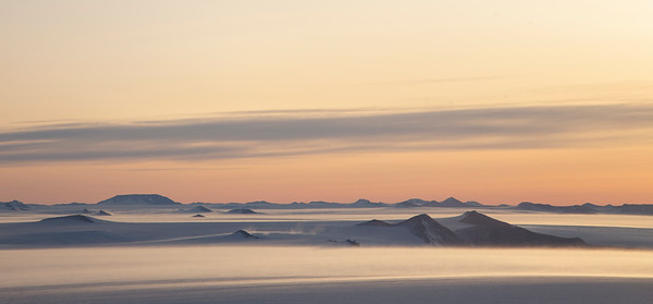 Sunset over the Shackleton Range with snow blowing off mountain peaks
