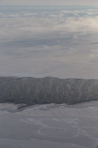 Steam escapes from relatively warm spots of open water & thin ice