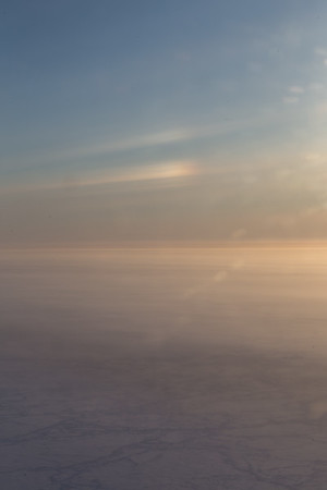 A sun dog glows from an icy cirrus cloud over sea ice