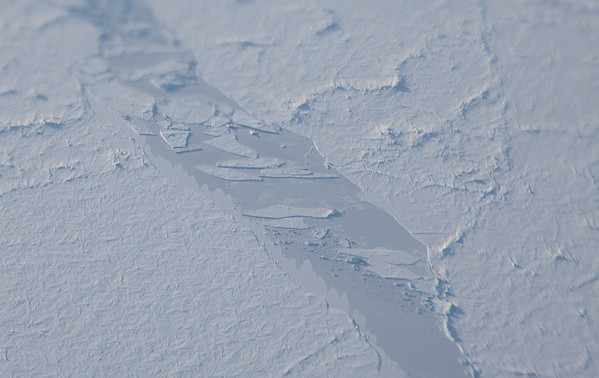 A refrozen sea ice lead with small floes and in it, drifted snow along the left edge
