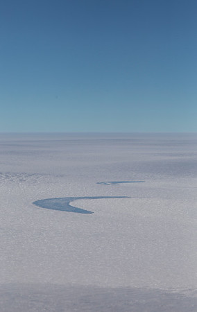 Two comma-shaped frozen melt ponds on 79N glacier