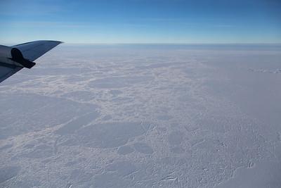 A collection of heavily crevassed multiyear sea ice floes meet smooth fast ice around northwest Essef Ringnes Island.