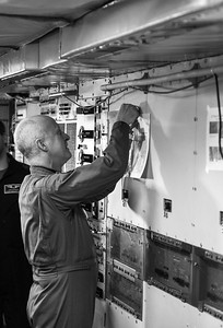 John puts today's flight details up on the wall for all to peruse