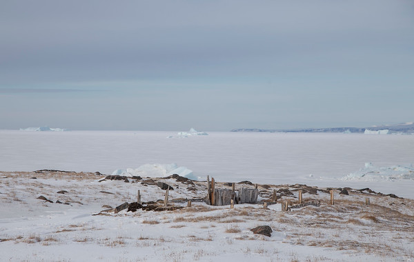 Remnants of an old Greenlandic sod house, with sea ice and icebergs in the distance