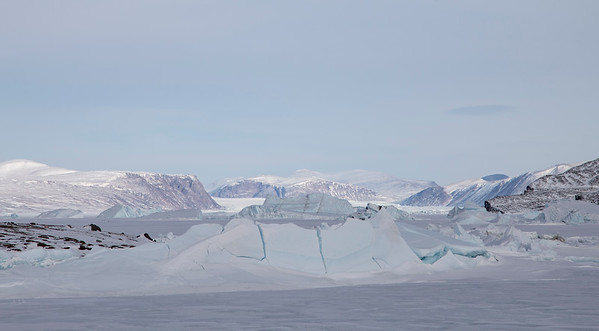 """A sea ice """"ice shove"""" along the shore, with icebergs and glaciers in the distance"""