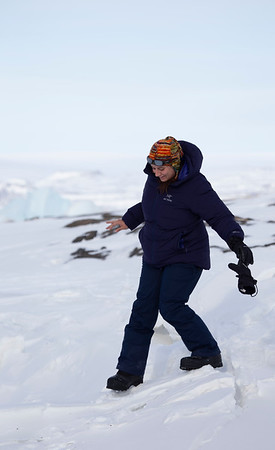 Eugenia climbing down into the tidal cracks of the sea ice near Dundas