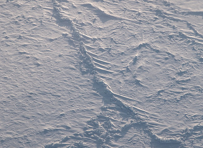 A large sea ice ridge with deep snow drifts off one side