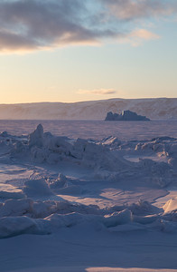 Snow-covered sea ice along the shore, shoved up into ridges due to the tides and wind