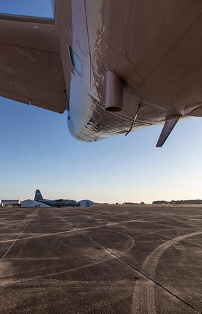 The tail of the P-3 reflects the morning sky