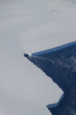 Seawater flowing out of a lead between icebergs, covered in a snow bridge