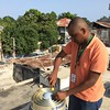 Renaldo Sauveur, Chief of  Geodesy and Leveling Services from Central National de I'Information Géo-Spatiale (CNIGS), replaces the LMA on the GPS antenna of station JME2, on the roof of the police headquarters in the town of Jacmel in southern Haiti. July 2016. (Photo/Mike Fend)
