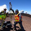 Amber Stillman and Margaux Mellott assist with a scan at the top of Mauna Kea. (Photo/Marianne Okal, UNAVCO)