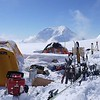 The campsite on Mount Hunter Plateau where the team spent ten days collecting samples, executing geophysical surveys, and installing a weather station. The yellow tent on the left is used by the research team as a cook tent for group meals and meetings. The dome tent in the center was used to store TLS, GPS, GPR and solar power charging for science and communication equipment. Skis were helpful to move on the deep snow at the study site and provided a means of recreation on the isolated glacier. Mount Foraker (17,400 ft) can be seen in the background. (Photo/Brendan Hodge, UNAVCO)