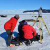 Researchers use UNAVCO TLS instruments on the sea ice to measure Weddell seal mass. Two scanners are used in unison to capture a volume measurement quickly without disturbing the resting seals. Project participants from left to right: Terrill Paterson (Montana State University), Brendan Hodge (UNAVCO), and Thierry Chambert (Montana State University). (Photo/Thomas Nylen, UNAVCO)