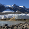 In mid-November, the field camp used by scientists lies across a frozen Lake Bonney from Blood Falls, seen here as a rusty red-orange channel at the toe of the Taylor Glacier. (Photo/Brendan Hodge, UNAVCO)