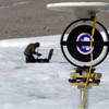 UNAVCO engineer Thomas Nylen installs a GPS instrument on the surface of the Taylor Glacier. Data from the GPS antenna on the TLS survey target in the foreground will be used to register and georeference Terrestrial LiDAR data. (Photo/Brendan Hodge, UNAVCO)