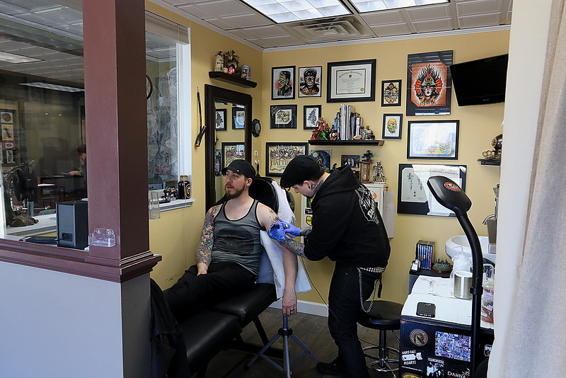 Tattoo artist Brad Touchette who works at Fight or Flight Tattoo Piercing on Summer Street in Fitchburg works on a piece of art on Isaac Aldrich's left arm at the shop on Tuesdsay morning, February 26, 2019. It was a ship in front of a moon. SENTINEL & ENTERPRISE/JOHN LOVE