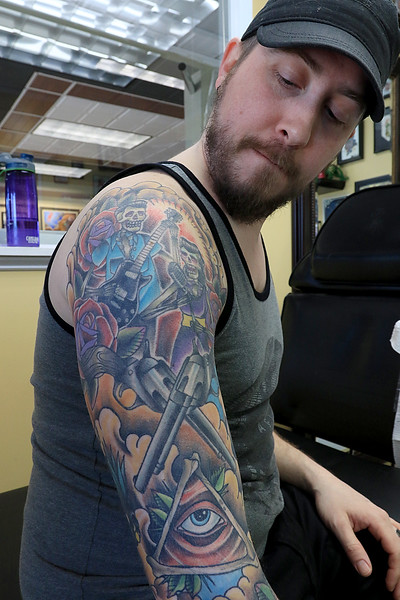 Isaac Aldrich looks at his sleeve on his right arm as he takes a break from getting a boat on his left arm done at Fight or Flight Tattoo Piercing on Summer Street in Fitchburg by tattoo artist Brad Touchette. SENTINEL & ENTERPRISE/JOHN LOVE