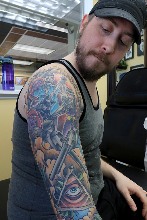 . Isaac Aldrich looks at his sleeve on his right arm as he takes a break from getting a boat on his left arm done at Fight or Flight Tattoo Piercing on Summer Street in Fitchburg by tattoo artist Brad Touchette. SENTINEL & ENTERPRISE/JOHN LOVE
