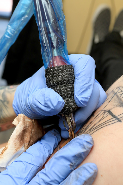 . Tattoo artist Brad Touchette who works at Fight or Flight Tattoo Piercing on Summer Street in Fitchburg works on a piece of art on Isaac Aldrich\'s left arm at the shop on Tuesdsay morning, February 26, 2019. It was a ship in front of a moon. SENTINEL & ENTERPRISE/JOHN LOVE