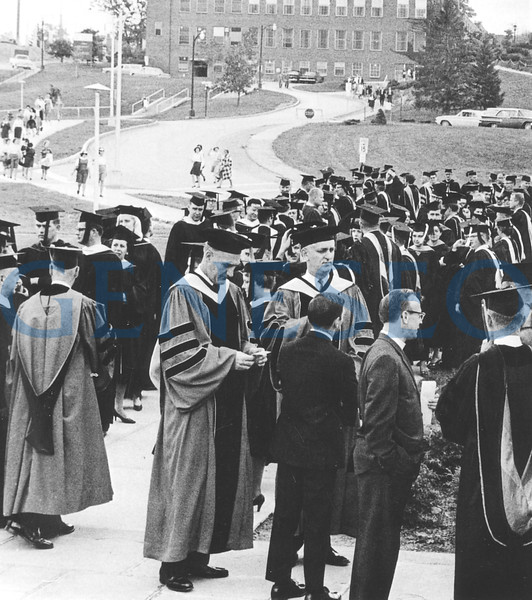 1963 MacVittie Named President<br /> Francis Moench retired, and Robert W. MacVittie—for whom the MacVittie College Union was named—became president, serving from 1963 until 1979, with a bonus stint as acting president in 1988–89. Photo: PResident Robert MacVittie and Vice President Lawrence Park headed the procession as faculty lined up west of the College Center (Blake A) for commencement in 1966. The Milne Library construction project appears in the left background. (1966 Oh Ha Daih)