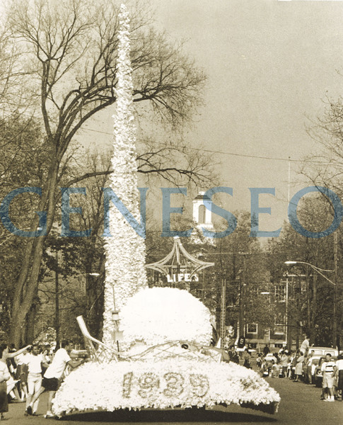 1953<br /> First Homecoming<br /> Geneseo's first Homecoming was held October 16 and 17 and featured a parade along Main Street. Students made grand entries and elaborate floats over the years, such as Phi Sigma Epsilon's 1963 float that celebrated the 1939 World's Fair with a trylon and perisphere. (The trylon and perisphere were hinged, so students could lower them to pass under power lines on Main Street.) Homecoming is now celebrated in partnership with Family Weekend.  Photo: Phi Sigma Epsilon's 1963 homecoming float depicting the 1939 World's Fair trylon and perisphere was hinged the trylon could be lowered to pass below power lines along the parade route. The hard work paid off with first-prize honors.