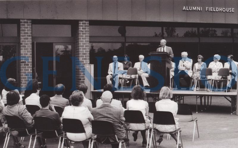1973 Alumni Fieldhouse Opened<br /> The Alumni Fieldhouse (now the Myrtle A. Merritt Athletic Center) contains the Ira S. Wilson Ice Arena, Louise Kuhl Gymnasium, the Alumni Pool, a fitness center, squash courts, and the offices of the athletic department staff. In 2004, the fieldhouse was renamed after Merritt, a generous supporter of the College who had held a number of college and statewide offices. Photo: Health, Physical Education and Recreation Department chair Daniel Mullin spoke at the 1973 Alumni Field House dedication. Others on the platform included Ira Wilson (extreme left), President and Mrs. MacVittie (right of lecturn), mayor Ann Duff (second from right) and athletic director Robert Riedel (extreme right). (Art Hatton)