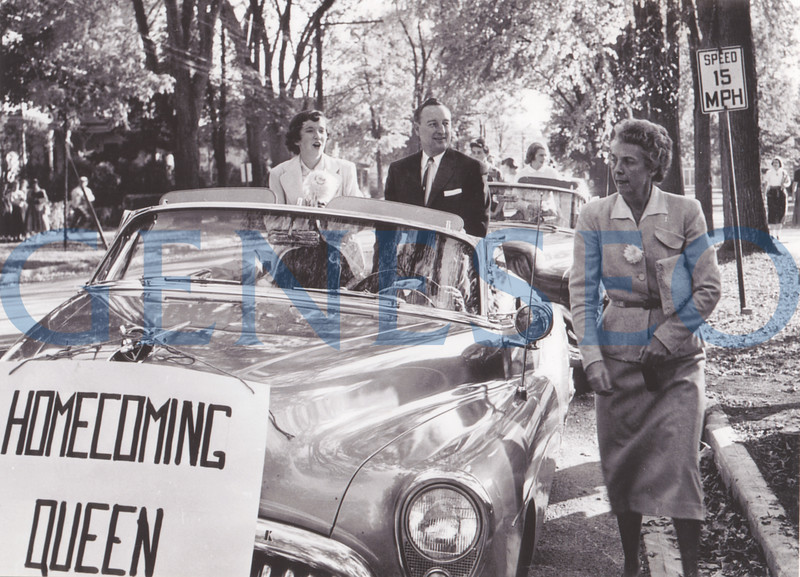 1953<br /> First Homecoming<br /> Geneseo's first Homecoming was held October 16 and 17 and featured a parade along Main Street. Students made grand entries and elaborate floats over the years, such as Phi Sigma Epsilon's 1963 float that celebrated the 1939 World's Fair with a trylon and perisphere. (The trylon and perisphere were hinged, so students could lower them to pass under power lines on Main Street.) Homecoming is now celebrated in partnership with Family Weekend. Photo: While waiting for the parade to begin, Queen Stephanie O'hara and Acting President Kenneth Freeman chatted with Dean Rosalind Fisher, gneeral chair of the parade.