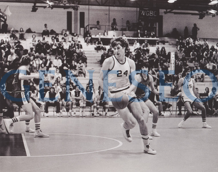 1975 First All-America Athletes<br /> Seven Geneseo student-athletes became the first in the college's history to earn All-America honors for men's basketball (Ed Robota '75), men's lacrosse (Gary Lewis '76), and swimming and diving (Richard Daggett '78, Larry Hoercher, Scott Holzchuh '77, Wayne Miller '80, Charles O'Donnell '76). Photo: Ed Robota (24). shown with teammate Gary Witter (15) in the new Alumni Field House gym in 1973, was Geneseo's first All-American in basketball. (Bright collection)