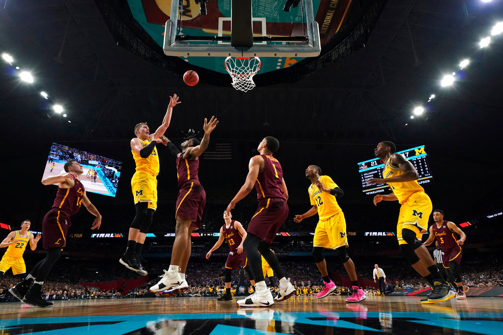. Michigan forward Moritz Wagner, left, shoots over Loyola-Chicago defenders during the second half in the semifinals of the Final Four NCAA college basketball tournament, Saturday, March 31, 2018, in San Antonio. (AP Photo/Chris Steppig, NCAA Photos Pool)