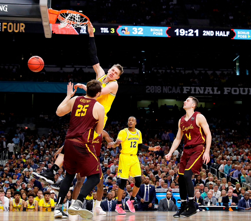 . Michigan forward Moritz Wagner dunks the ball over Loyola-Chicago center Cameron Krutwig (25) during the second half in the semifinals of the Final Four NCAA college basketball tournament, Saturday, March 31, 2018, in San Antonio. (AP Photo/David J. Phillip)