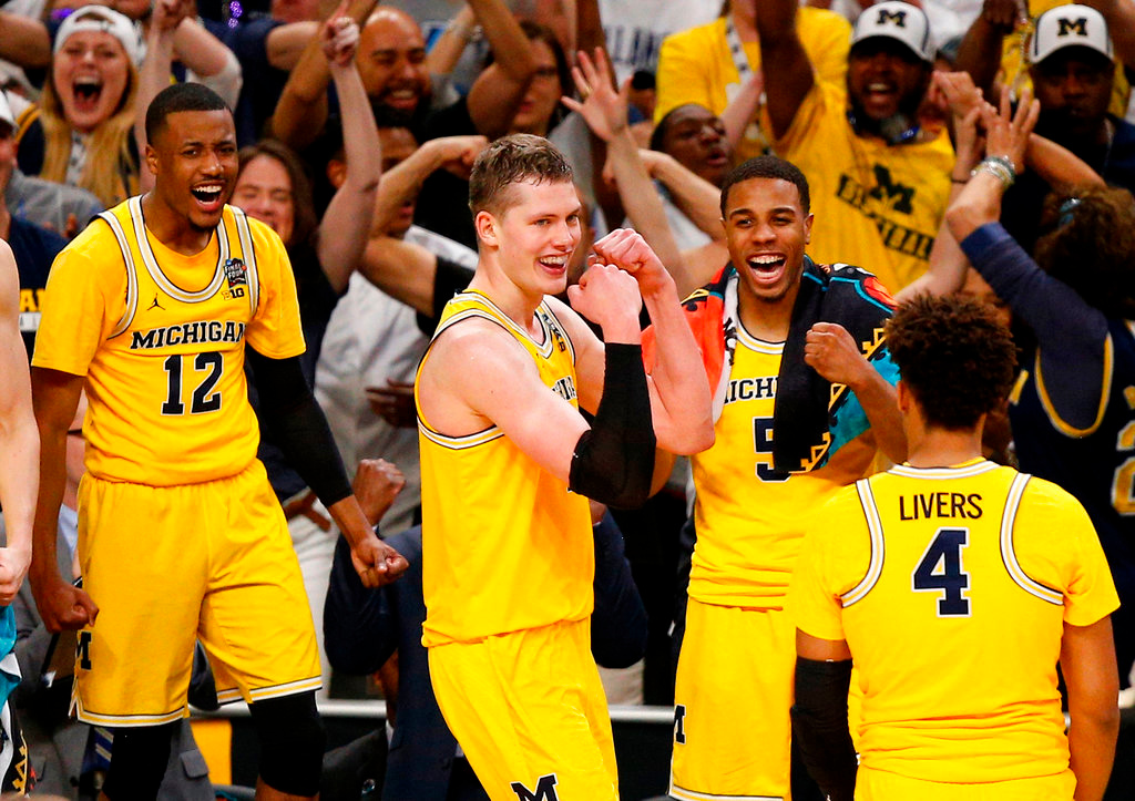 . Michigan\'s Moritz Wagner, second from left, celebrates with his teammates during the second half in the semifinals of the Final Four NCAA college basketball tournament against Loyola-Chicago, Saturday, March 31, 2018, in San Antonio. (AP Photo/Brynn Anderson)
