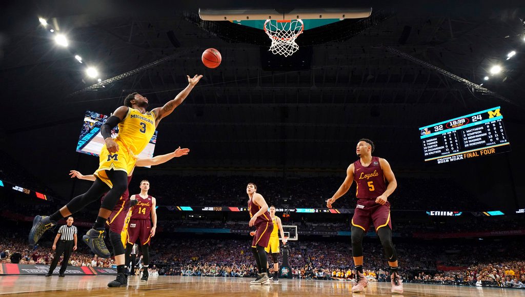 . Michigan guard Zavier Simpson (3) drives to the basket in front of Loyola-Chicago guard Marques Townes (5) during the second half in the semifinals of the Final Four NCAA college basketball tournament, Saturday, March 31, 2018, in San Antonio. Michigan won 69-57. (AP Photo/Chris Steppig, NCAA Photos Pool)