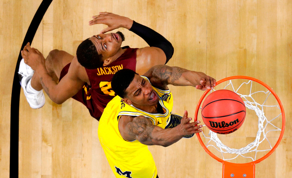 . Michigan guard Charles Matthews dunks the ball ahead of Loyola-Chicago forward Aundre Jackson, left, during the first half in the semifinals of the Final Four NCAA college basketball tournament, Saturday, March 31, 2018, in San Antonio. (AP Photo/Eric Gay)