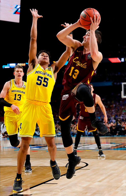 . Loyola-Chicago guard Clayton Custer (13) shoots over Michigan guard Eli Brooks (55) during the first half in the semifinals of the Final Four NCAA college basketball tournament, Saturday, March 31, 2018, in San Antonio. (AP Photo/David J. Phillip)