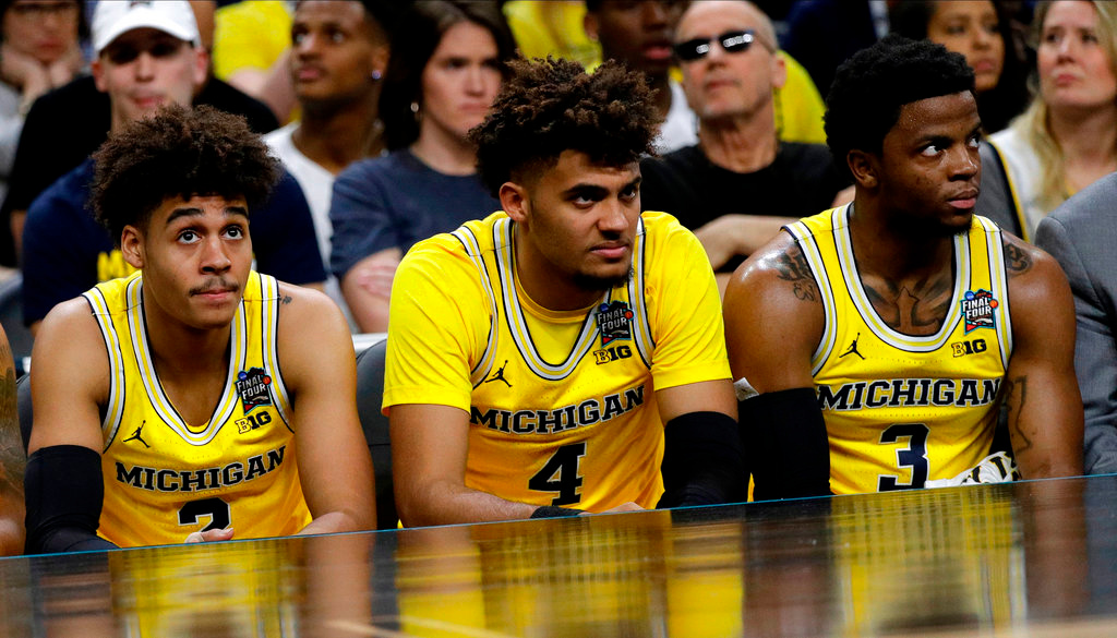 . Michigan\'s Jordan Poole, from left, Isaiah Livers and Zavier Simpson watch from the bench during the second half against Loyola-Chicago in the semifinals of the Final Four NCAA college basketball tournament, Saturday, March 31, 2018, in San Antonio. (AP Photo/David J. Phillip)