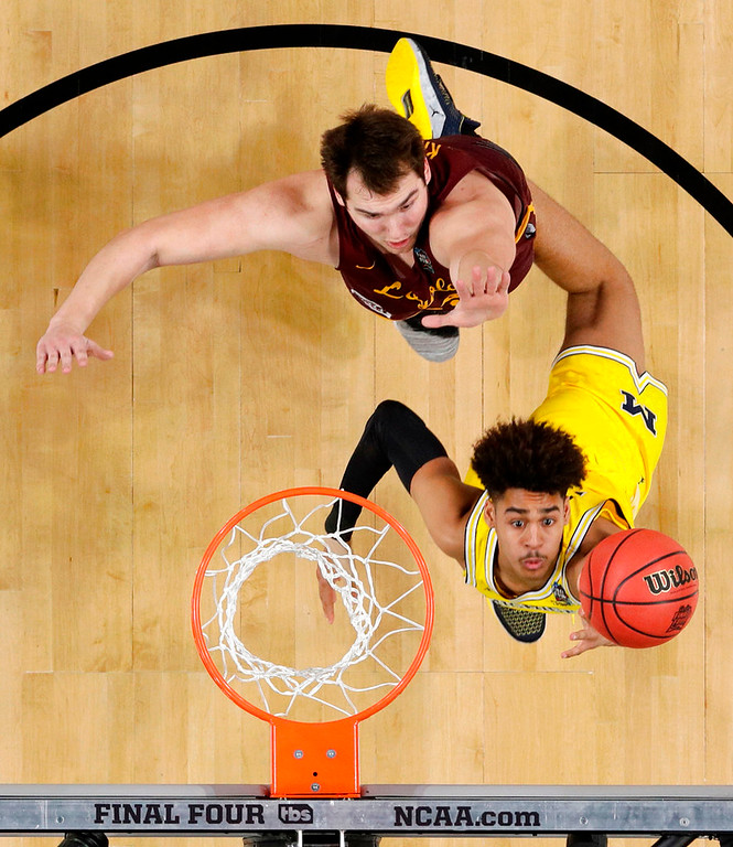 . Michigan guard Jordan Poole drives to the basket past Loyola-Chicago center Cameron Krutwig, top, during the second half in the semifinals of the Final Four NCAA college basketball tournament, Saturday, March 31, 2018, in San Antonio. (AP Photo/David J. Phillip)