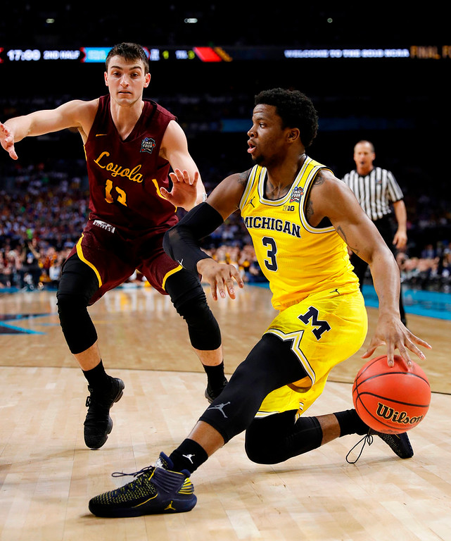 . Michigan\'s Zavier Simpson (3) drives the ball against Loyola-Chicago\'s Clayton Custer (13) during the second half in the semifinals of the Final Four NCAA college basketball tournament, Saturday, March 31, 2018, in San Antonio. (AP Photo/David J. Phillip)