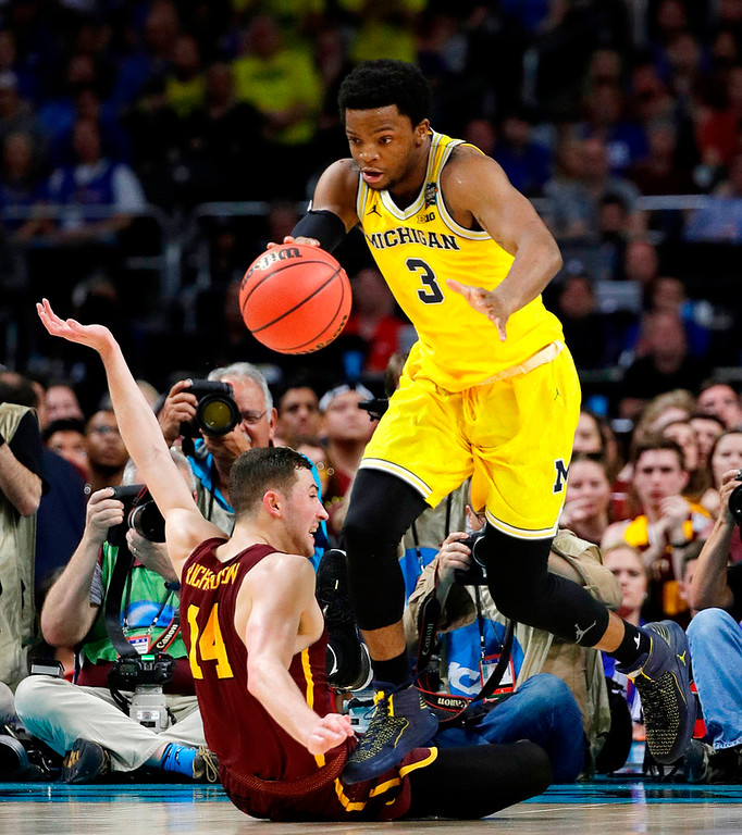. Michigan\'s Zavier Simpson (3) drives the ball against Loyola-Chicago\'s Ben Richardson (14) during the second half in the semifinals of the Final Four NCAA college basketball tournament, Saturday, March 31, 2018, in San Antonio. (AP Photo/David J. Phillip)