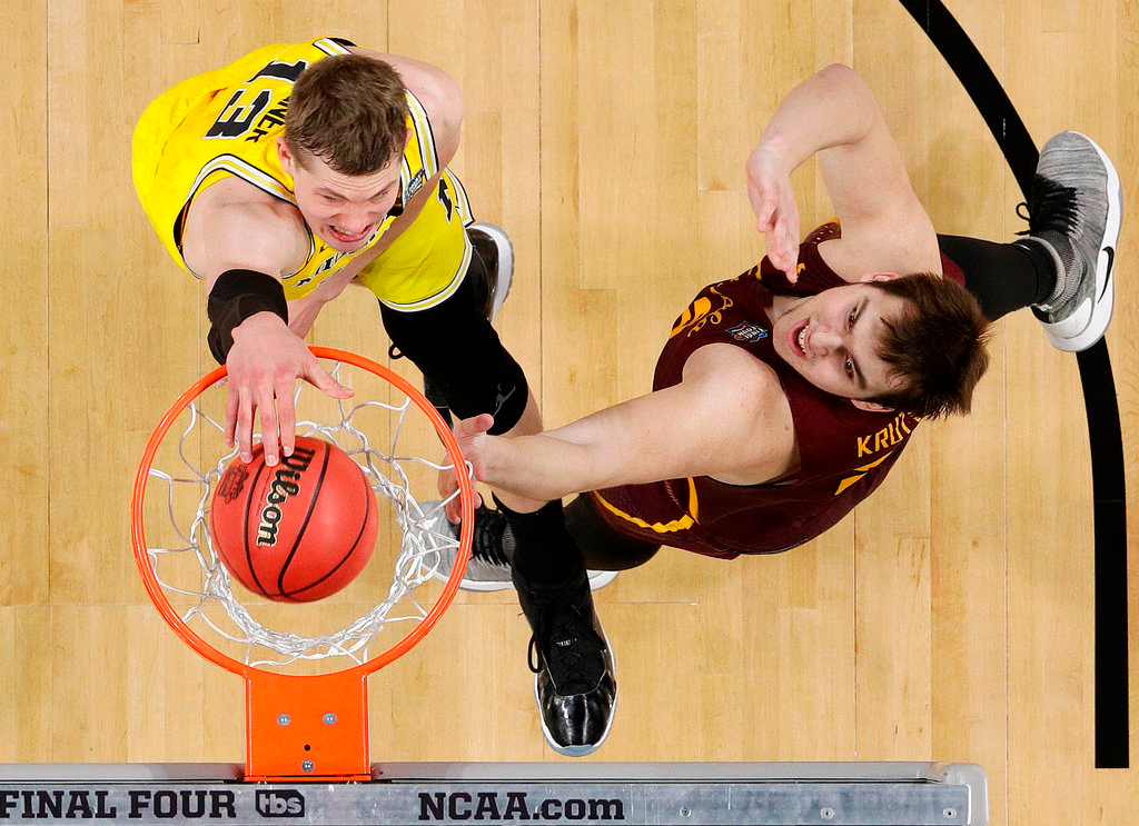 . Michigan\'s Moritz Wagner (13) dunks over Loyola-Chicago\'s Cameron Krutwig (25) during the first half in the semifinals of the Final Four NCAA college basketball tournament, Saturday, March 31, 2018, in San Antonio. (AP Photo/David J. Phillip)