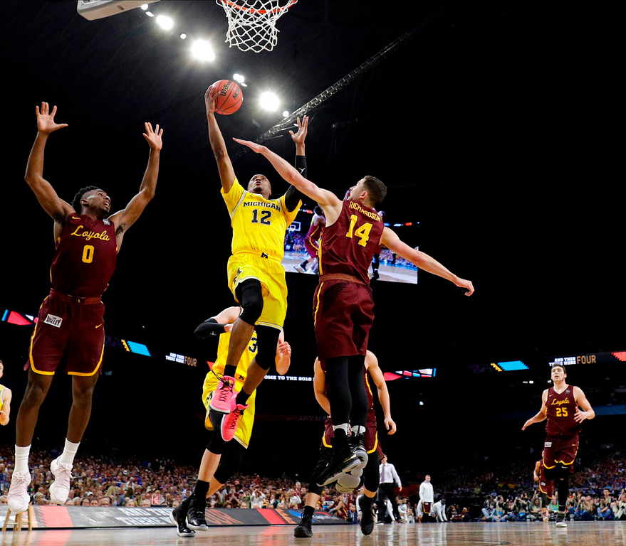 . Michigan guard Muhammad-Ali Abdur-Rahkman (12) drives to the basket between Loyola-Chicago\'s Donte Ingram, left, and Ben Richardson during the second half in the semifinals of the Final Four NCAA college basketball tournament, Saturday, March 31, 2018, in San Antonio. (AP Photo/David J. Phillip)