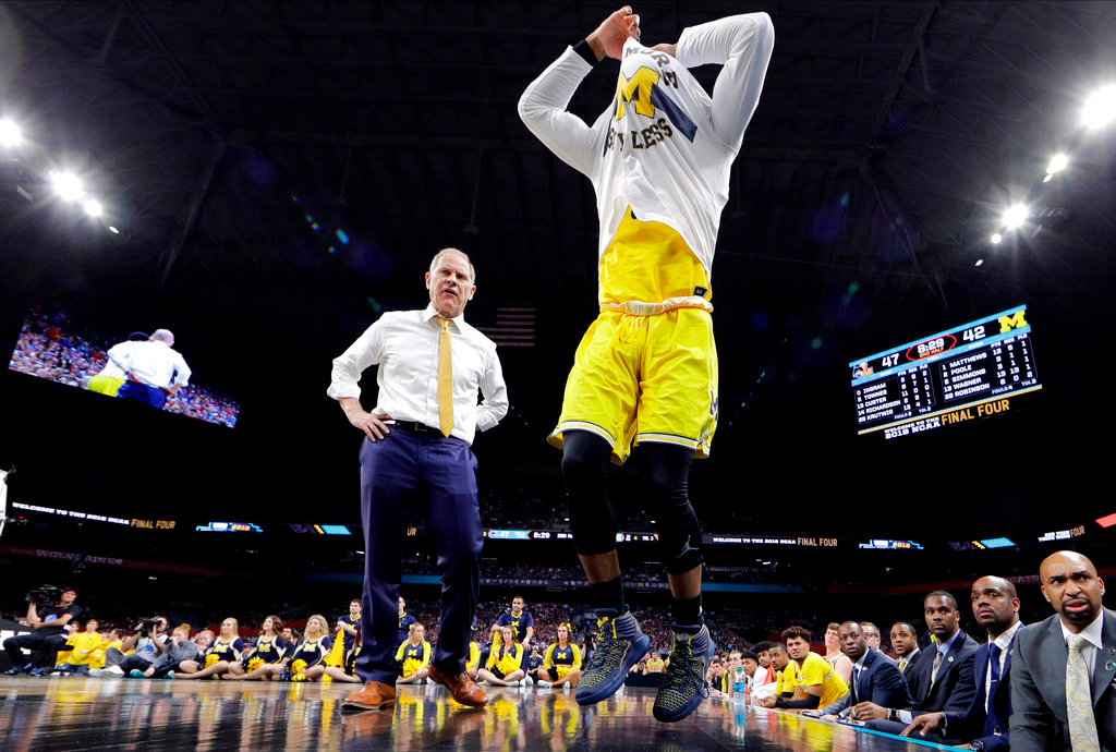 . Michigan head coach John Beilein talks to Zavier Simpson during the second half in the semifinals of the Final Four NCAA college basketball tournament against Loyola-Chicago, Saturday, March 31, 2018, in San Antonio. (AP Photo/David J. Phillip)