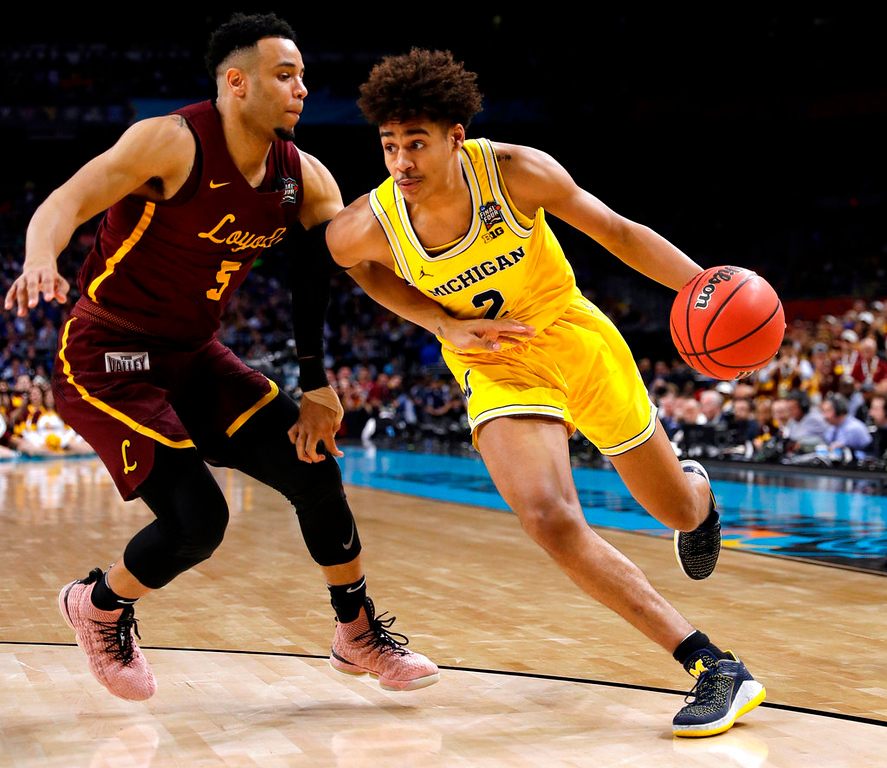 . Michigan guard Jordan Poole drives past Loyola-Chicago guard Marques Townes, left, during the second half in the semifinals of the Final Four NCAA college basketball tournament, Saturday, March 31, 2018, in San Antonio. (AP Photo/David J. Phillip)