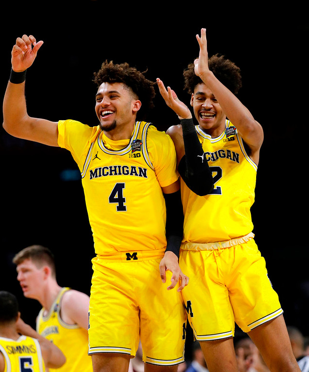 . Michigan forward Isaiah Livers (4) celebrates with teammate Jordan Poole during the second half against Loyola-Chicago in the semifinals of the Final Four NCAA college basketball tournament, Saturday, March 31, 2018, in San Antonio. (AP Photo/David J. Phillip)