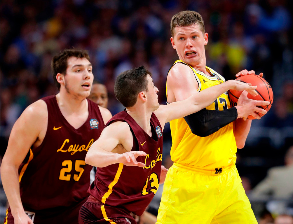 . Loyola-Chicago guard Clayton Custer, center, tries to steal the ball from Michigan forward Moritz Wagner, right, during the second half in the semifinals of the Final Four NCAA college basketball tournament, Saturday, March 31, 2018, in San Antonio. (AP Photo/Eric Gay)