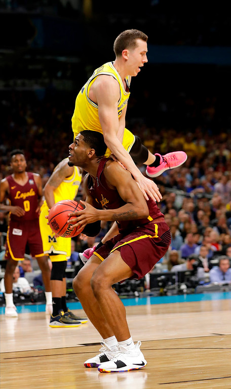 . Michigan\'s Duncan Robinson fouls as Loyola-Chicago\'s Aundre Jackson tries to shoot during the second half in the semifinals of the Final Four NCAA college basketball tournament, Saturday, March 31, 2018, in San Antonio. (AP Photo/Eric Gay)