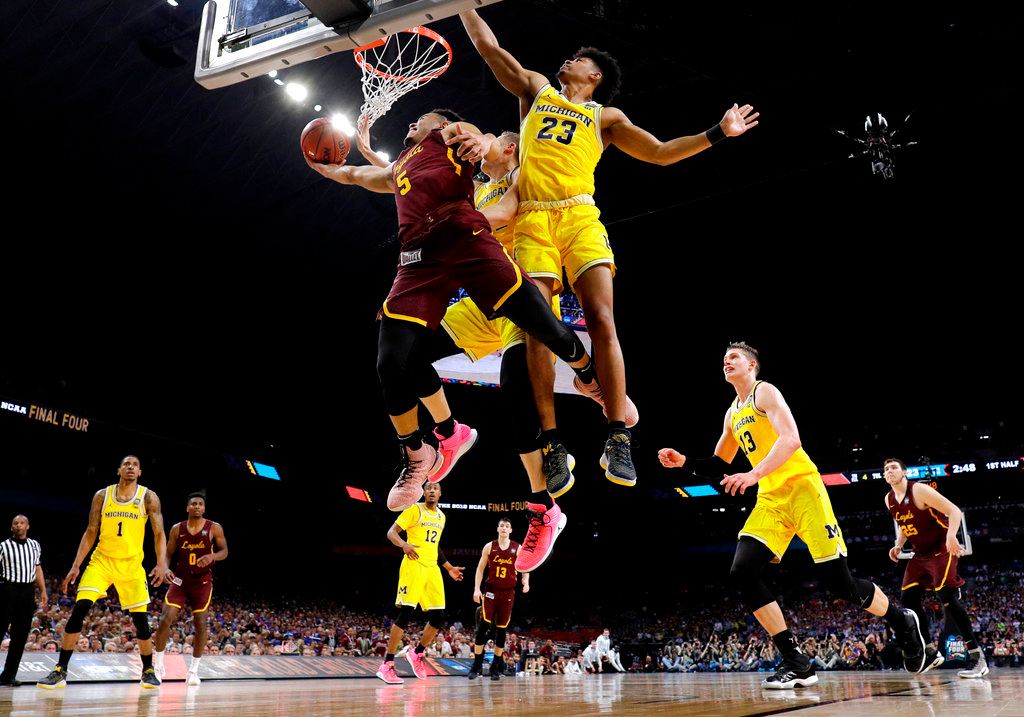 . Loyola-Chicago guard Marques Townes (5) drives to the basket past Michigan guard Ibi Watson (23) during the first half in the semifinals of the Final Four NCAA college basketball tournament, Saturday, March 31, 2018, in San Antonio. (AP Photo/David J. Phillip)