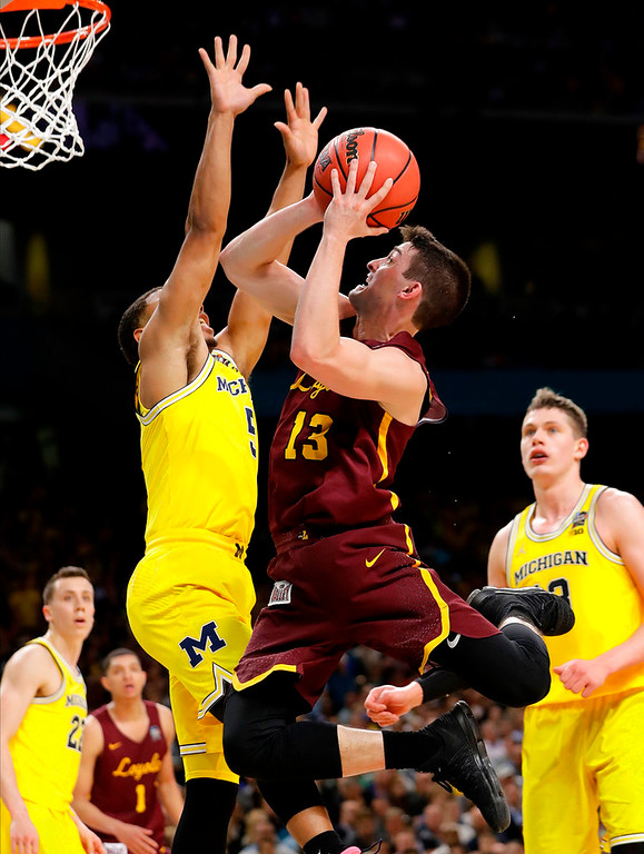 . Loyola-Chicago\'s Clayton Custer (13) shoots against Michigan\'s Jaaron Simmons (5) during the second half in the semifinals of the Final Four NCAA college basketball tournament, Saturday, March 31, 2018, in San Antonio. (AP Photo/Eric Gay)