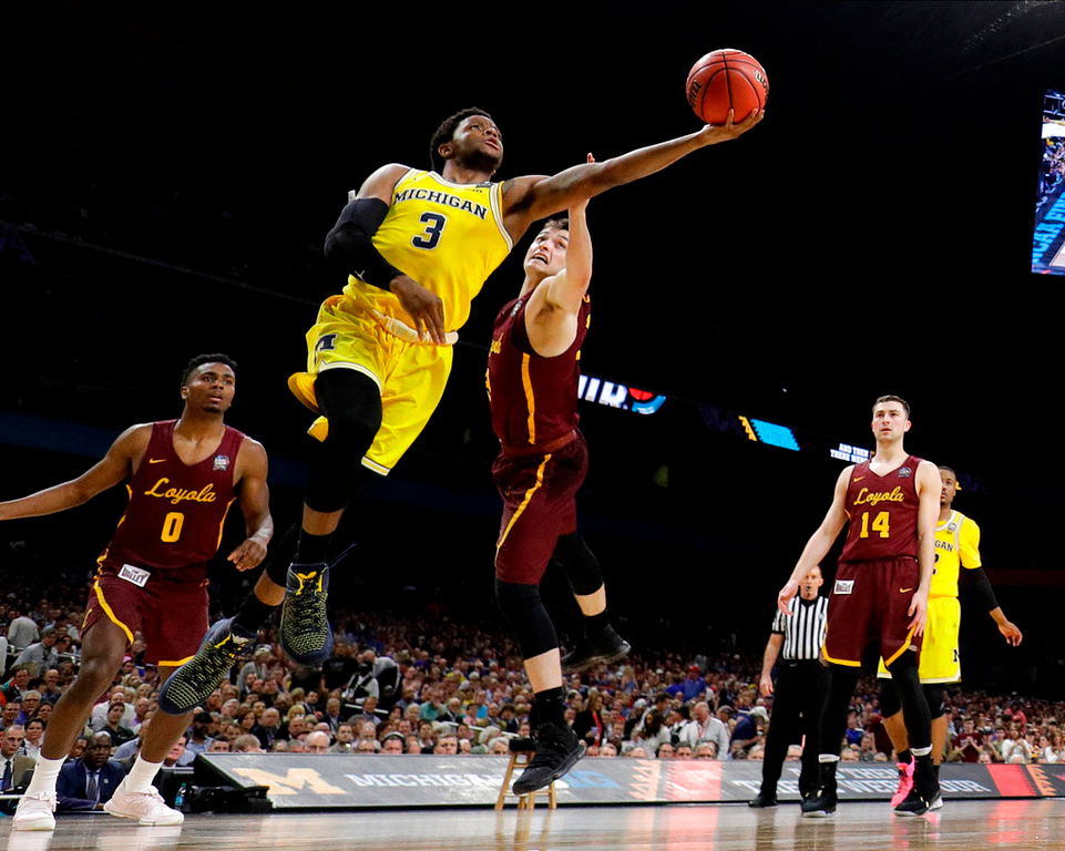 . Michigan guard Zavier Simpson (3) drives to the basket between Loyola-Chicago\'s Donte Ingram, left, and Clayton Custer during the second half in the semifinals of the Final Four NCAA college basketball tournament, Saturday, March 31, 2018, in San Antonio. (AP Photo/David J. Phillip)